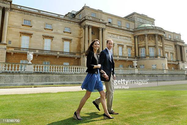 Prince William Duke of Cambridge and Catherine Duchess of Cambridge walk hand in hand from Buckingham Palace the day after their wedding to a waiting...