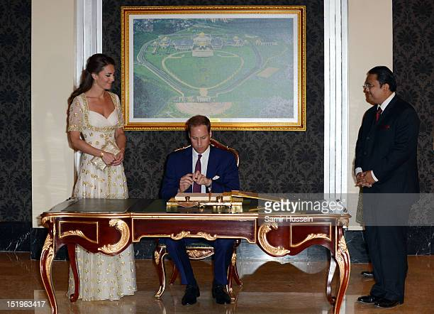 Prince William Duke of Cambridge and Catherine Duchess of Cambridge sign the visitors' book during an official dinner hosted by Malaysia's Head of...