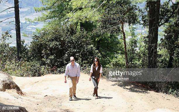 Prince William Duke of Cambridge and Catherine Duchess of Cambridge pose next to a prayer wheel on the trek up to Tiger's Nest during a visit to...