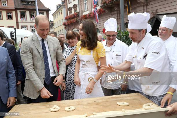 Prince William Duke of Cambridge and Catherine Duchess of Cambridge attempt to make pretzels during a tour of a traditional German market in the...
