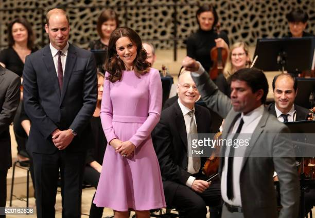 Prince William Duke of Cambridge and Catherine Duchess of Cambridge receive a quick lesson to conduct an orchestra at Elbphilharmonie during day...