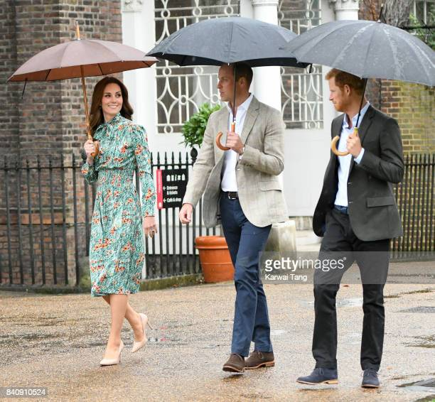 Prince William Duke of Cambridge and Catherine Duchess of Cambridge with Prince Harry during a visit to The Sunken Garden at Kensington Palace on...