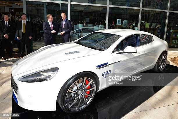 Prince William Duke of Cambridge and Mark Palmer CEO of Aston Martin pose with an Aston Martin Rapide S during a visit to the British designed...
