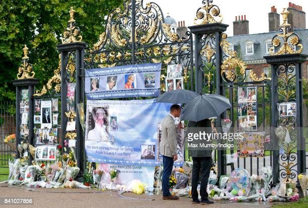 Prince William Duke of Cambridge and Prince Harry view tributes to Diana Princess of Wales left at the gates of Kensington Palace after visiting the...