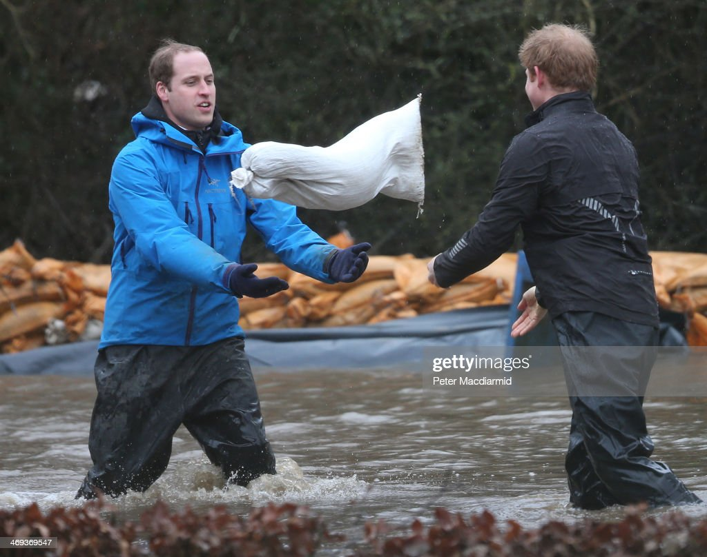 Prince William, Duke of Cambridge (L) catches a sandbag thrown by his brother <a gi-track='captionPersonalityLinkClicked' href=/galleries/search?phrase=Prince+Harry&family=editorial&specificpeople=178173 ng-click='$event.stopPropagation()'>Prince Harry</a> as they build a flood defence wall at Eton End School on February 14, 2014 in Datchet, England. Flood water has remained high in some areas and high winds are causing disruption to other parts of the UK with the Met Office issuing a red weather warning.
