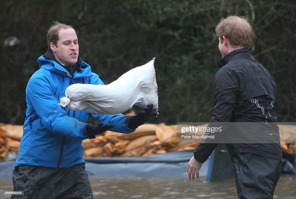 Prince William, Duke of Cambridge (L) catches a sandbag thrown by his brother Prince Harry as they build a flood defence wall at Eton End School on February 14, 2014 in Datchet, England. Flood water has remained high in some areas and high winds are causing disruption to other parts of the UK with the Met Office issuing a red weather warning.
