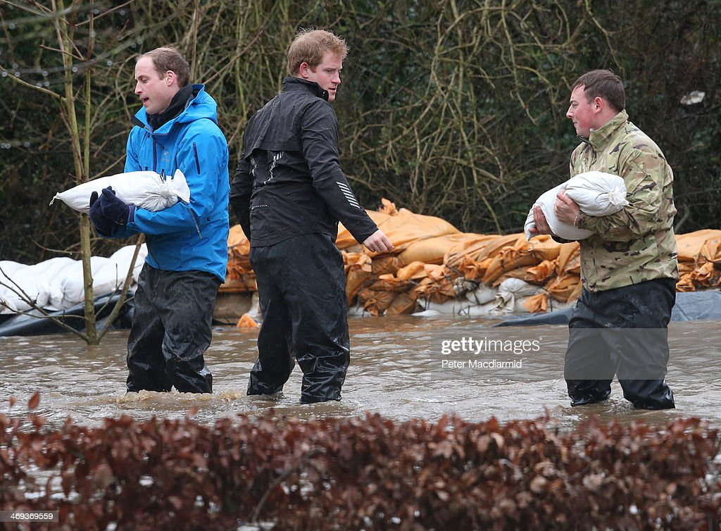 Prince William, Duke of Cambridge (L) catches a sandbag thrown by his brother Prince Harry as they help soldiers build a flood defence wall at Eton End School on February 14, 2014 in Datchet, England. Flood water has remained high in some areas and high winds are causing disruption to other parts of the UK with the Met Office issuing a red weather warning.