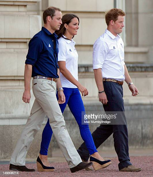 Prince William Duke of Cambridge Catherine Duchess of Cambridge and Prince Harry walk into the forecourt of Buckingham Palace to await the arrival of...