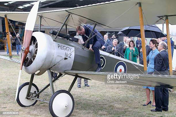 Prince William Duke of Cambridge climbs in to the cockpit of a WWI Sopwith Pup biplane as Catherine Duchess of Cambridge looks on during a visit to...
