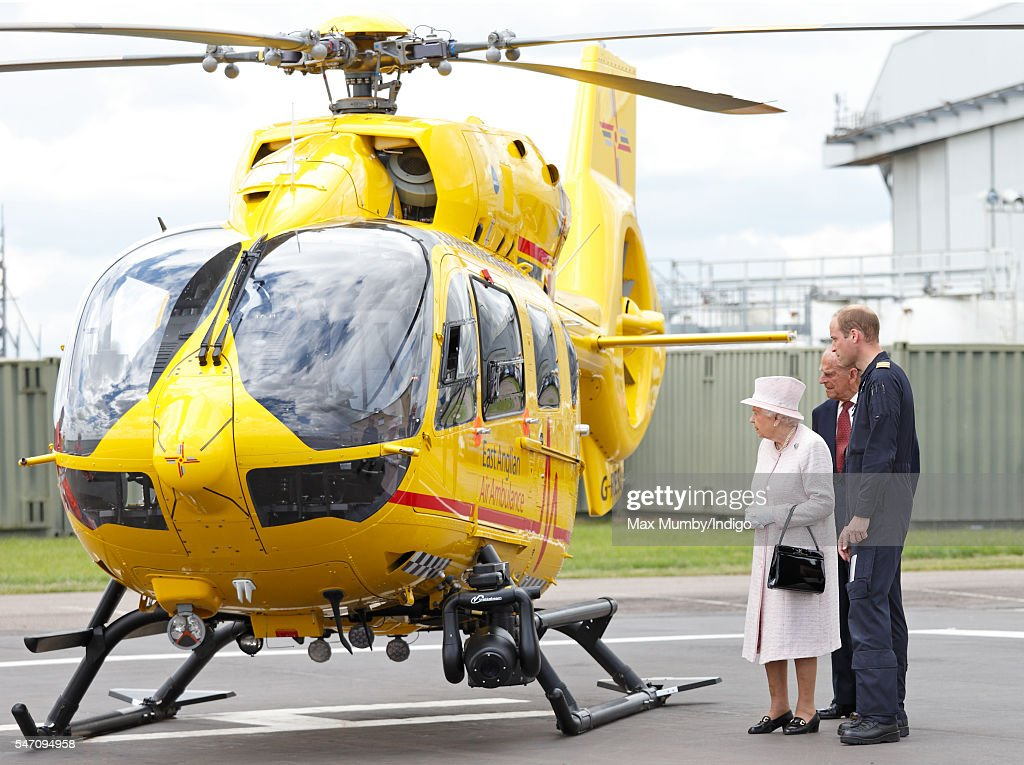 Prince William, Duke of Cambridge gives his grandparents Queen Elizabeth II and Prince Philip, Duke of Edinburgh a tour of his air ambulance helicopter as they open the new East Anglian Air Ambulance base at Cambridge Airport on July 13, 2016 in Cambridge, England.