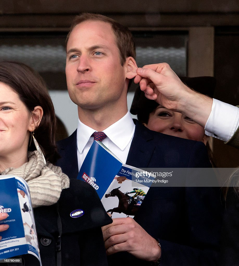 Prince William, Duke of Cambridge has his ear pulled by a friend as he and <a gi-track='captionPersonalityLinkClicked' href=/galleries/search?phrase=Catherine+-+Duchesse+de+Cambridge&family=editorial&specificpeople=542588 ng-click='$event.stopPropagation()'>Catherine</a>, Duchess of Cambridge watch the racing on Day 4 of The Cheltenham Festival at Cheltenham Racecourse on March 15, 2013 in London, England.