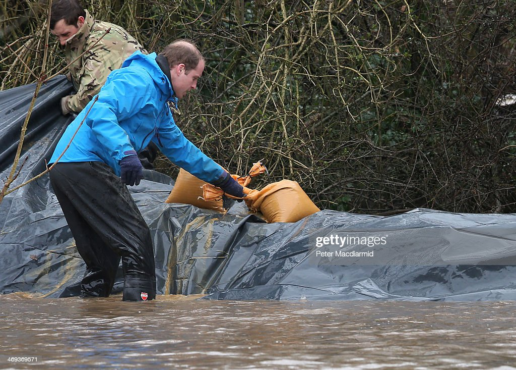 Prince William, Duke of Cambridge helps build a flood defence wall at Eton End School on February 14, 2014 in Datchet, England. Flood water has remained high in some areas and high winds are causing disruption to other parts of the UK with the Met Office issuing a red weather warning.