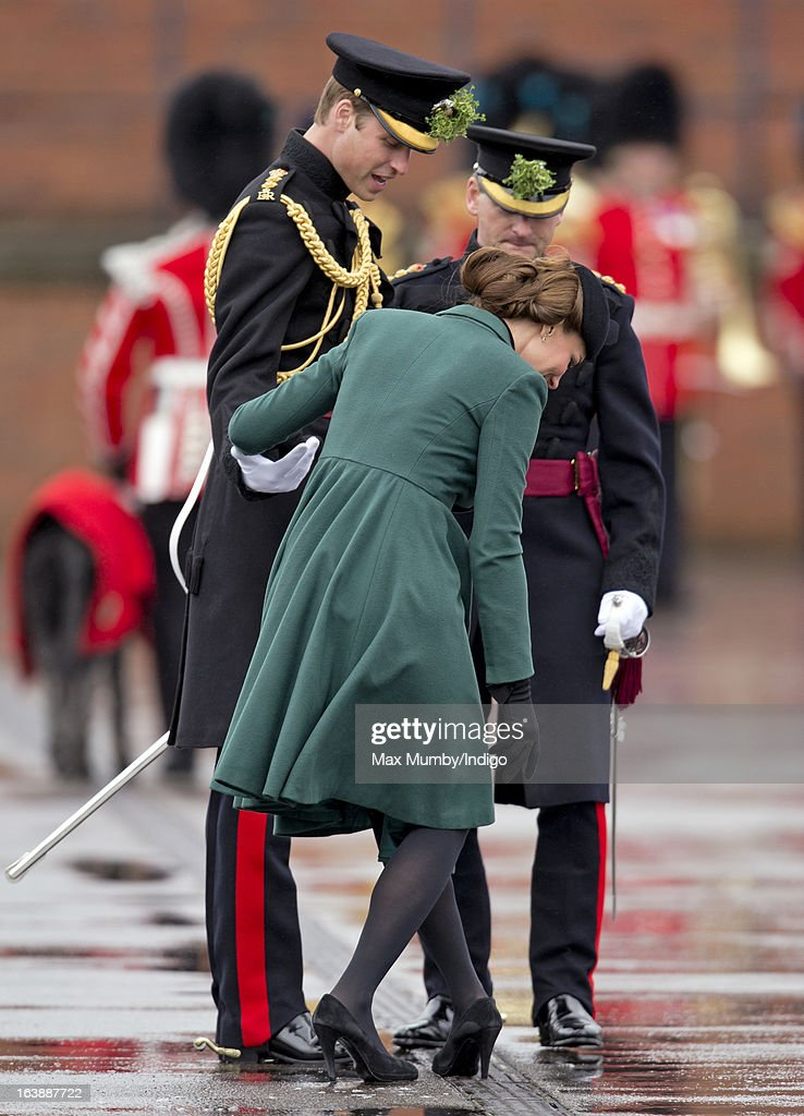 Prince William, Duke of Cambridge (in his role as Colonel of the Regiment) helps his wife <a gi-track='captionPersonalityLinkClicked' href=/galleries/search?phrase=Catherine+-+Herzogin+von+Cambridge&family=editorial&specificpeople=542588 ng-click='$event.stopPropagation()'>Catherine</a>, Duchess of Cambridge as she gets the heel of her shoe stuck in a grate as they attend the St Patrick's Day Parade at Mons Barracks on March 17, 2013 in Aldershot, England.