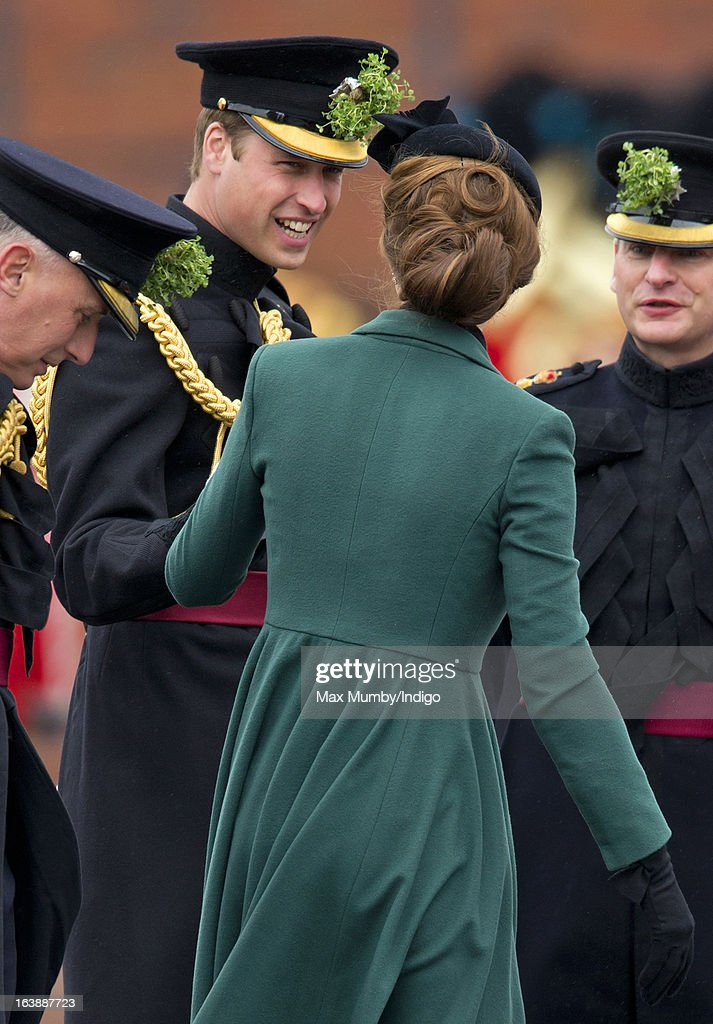 Prince William, Duke of Cambridge (in his role as Colonel of the Regiment) helps his wife Catherine, Duchess of Cambridge as she gets the heel of her shoe stuck in a grate as they attend the St Patrick's Day Parade at Mons Barracks on March 17, 2013 in Aldershot, England.