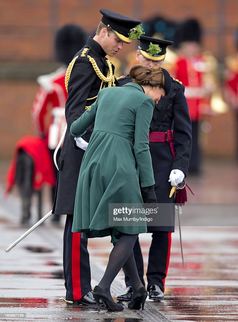 Prince William, Duke of Cambridge (in his role as Colonel of the Regiment) helps his wife <a gi-track='captionPersonalityLinkClicked' href=/galleries/search?phrase=Catherine+-+Duquesa+de+Cambridge&family=editorial&specificpeople=542588 ng-click='$event.stopPropagation()'>Catherine</a>, Duchess of Cambridge as she gets the heel of her shoe stuck in a grate as they attend the St Patrick's Day Parade at Mons Barracks on March 17, 2013 in Aldershot, England.