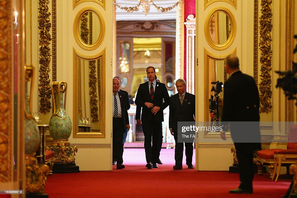 Prince William, Duke of Cambridge in his role as The President of The Football Association arrives with FA Chairman <a gi-track='captionPersonalityLinkClicked' href=/galleries/search?phrase=Greg+Dyke&family=editorial&specificpeople=207080 ng-click='$event.stopPropagation()'>Greg Dyke</a> before awarding medals to 150 grassroots heroes for their outstanding contribution and service to football. The Ceremony at Buckingham Palace took place as part of The FA's 150th anniversary at Buckingham Palace on October 7, 2013 in London, England.