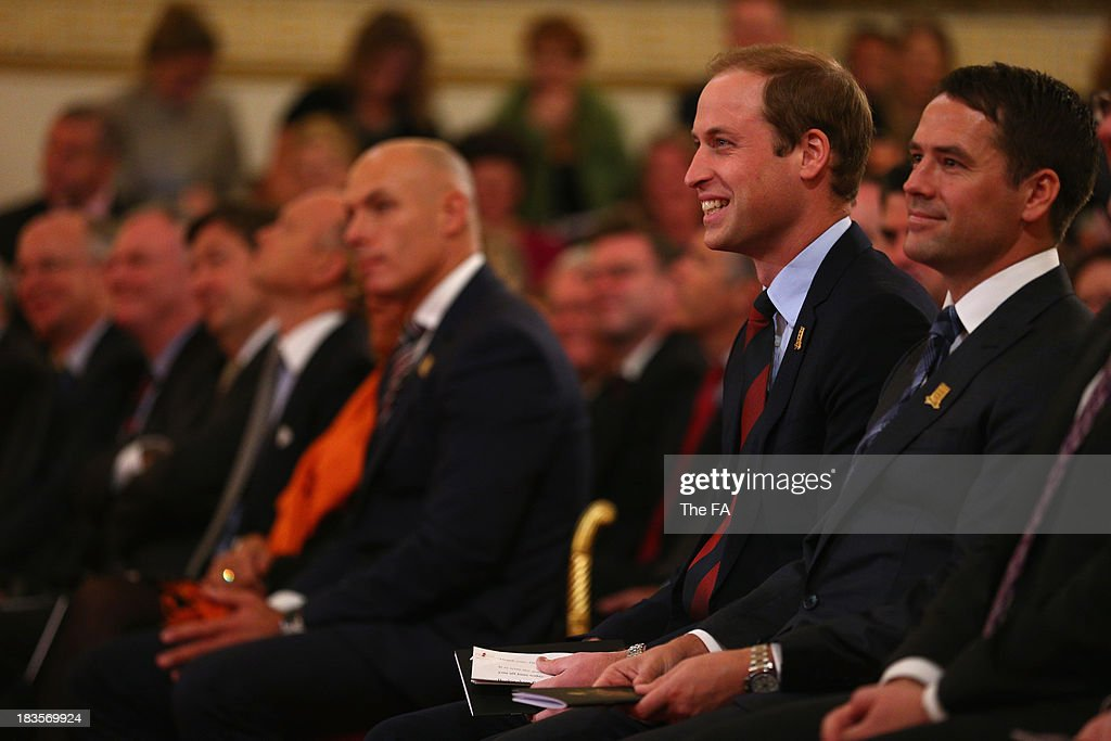 Prince William, Duke of Cambridge in his role as The President of The Football Association looks on alongside Michael Owen before awarding medals to 150 grassroots heroes for their outstanding contribution and service to football. The Ceremony at Buckingham Palace took place as part of The FA's 150th anniversary at Buckingham Palace on October 7, 2013 in London, England.