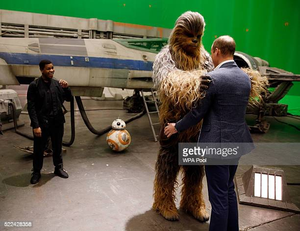 Prince William Duke of Cambridge is greeted by Chewbacca as British actor John Boyega watches during a tour of the Star Wars sets at Pinewood studios...