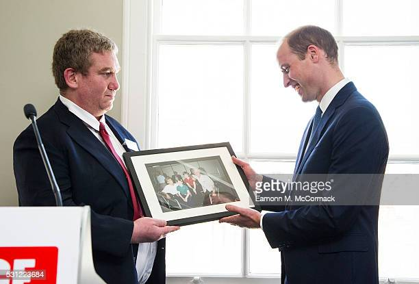Prince William Duke of Cambridge is presented with a picture of himself Prince Harry and Princess Diana taken during a visit to The Passage in 1994...