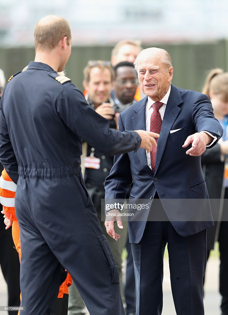 Prince William, Duke of Cambridge jokes with Prince Philip, Duke of Edinburgh as he says goodbye after visiting the new East Anglian Air Ambulance Base at Cambridge Airport on July 13, 2016 in Cambridge, England.