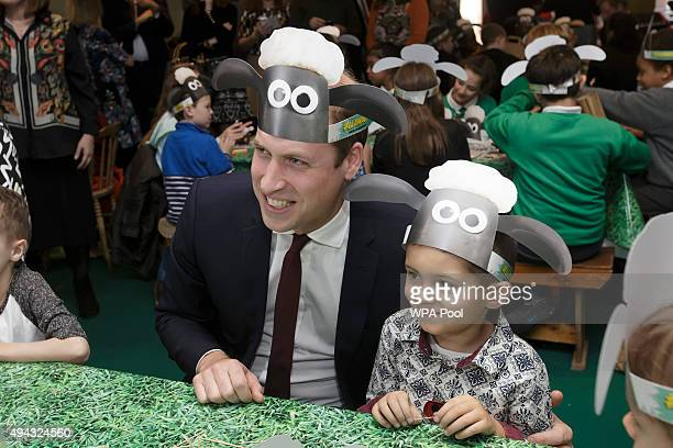 Prince William Duke of Cambridge left poses for photographs wearing a Shaun the Sheep hat with children and representatives from charities and...