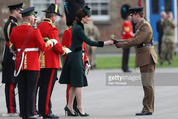 Prince William Duke of Cambridge looks on as Catherine Duchess of Cambridge presents the 1st Battalion Irish Guardsmen with shamrocks during the...