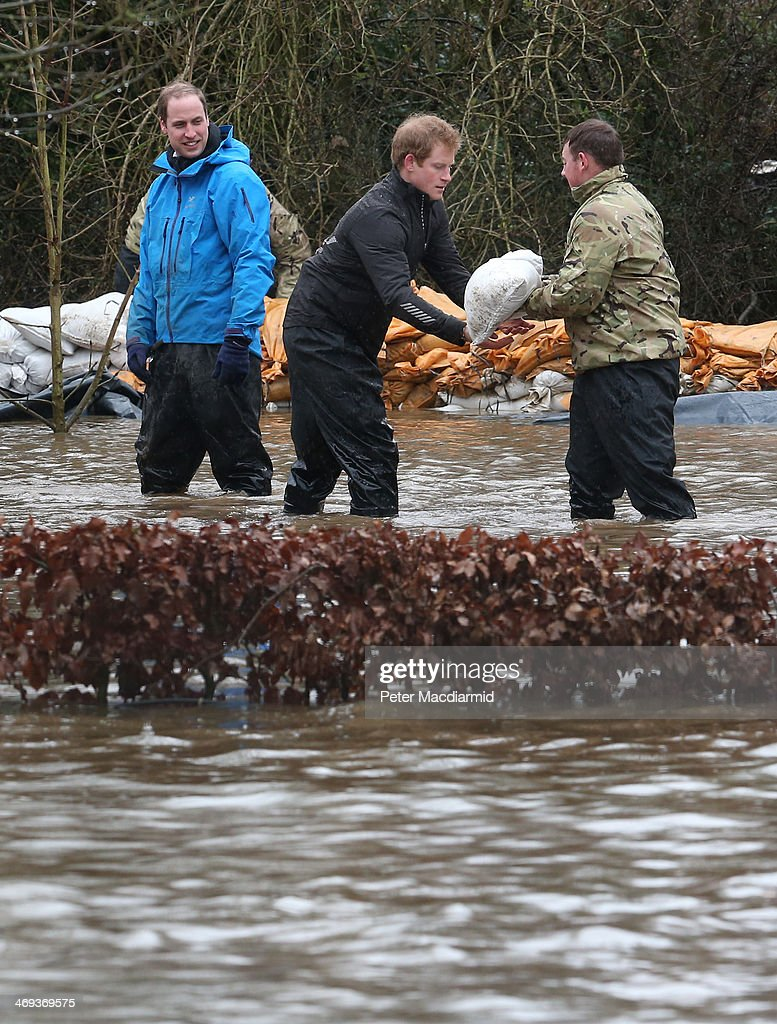 Prince William, Duke of Cambridge (L) looks on as his brother Prince Harry receives a sandbag from a soldier as they build a flood defence wall at Eton End School on February 14, 2014 in Datchet, England. Flood water has remained high in some areas and high winds are causing disruption to other parts of the UK with the Met Office issuing a red weather warning.