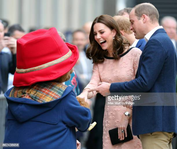 Prince William Duke of Cambridge looks on as Paddington Bear greets Catherine Duchess of Cambridge whilst they attend the Charities Forum Event at...