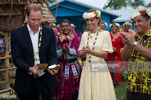 Prince William Duke of Cambridge opens a coconut with a machete as Catherine Duchess of Cambridge watches on September 18 2012 in Tuvalu Prince...