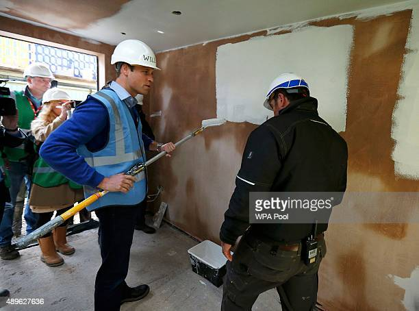 Prince William Duke of Cambridge paints a wall as he helps to renovate homes for exservice personnel as part of the BBC television DIY SOS series on...