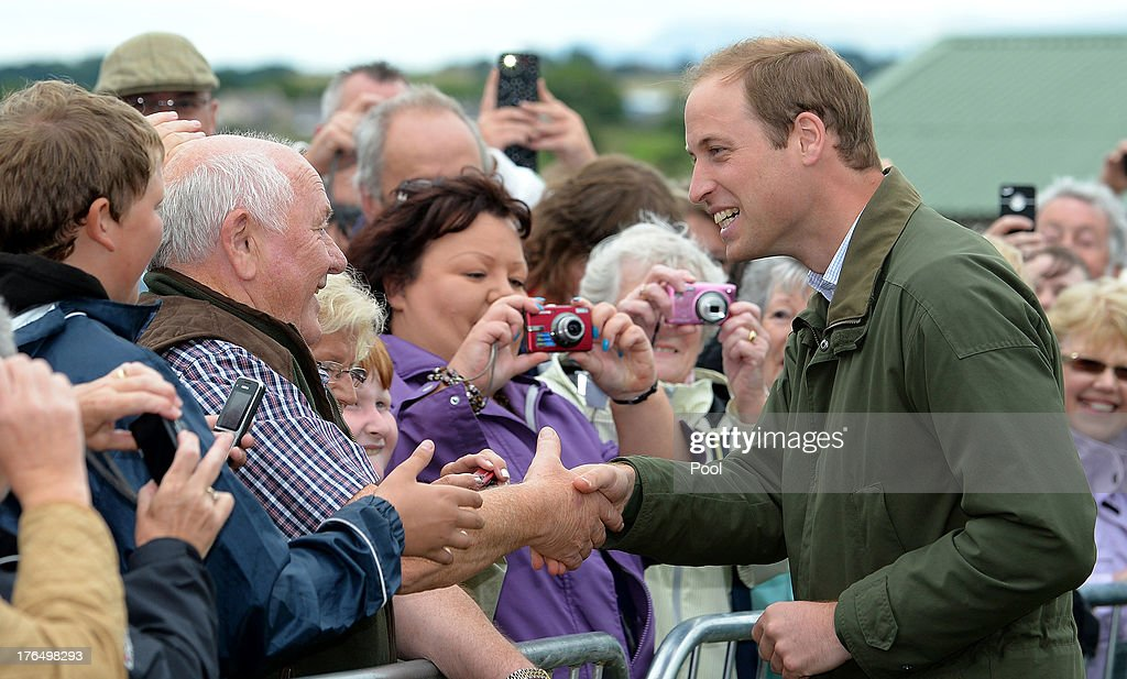 Prince William, Duke of Cambridge pets a dog during his visit at Anglesey agricultural show on his first official engagement since the birth of his son Prince George of Cambridge last month at Anglesey Showground on August 14, 2013 in Bangor, Wales. Prince William had two weeks parental leave from work as a RAF rescue helicopter pilot in Anglesey.