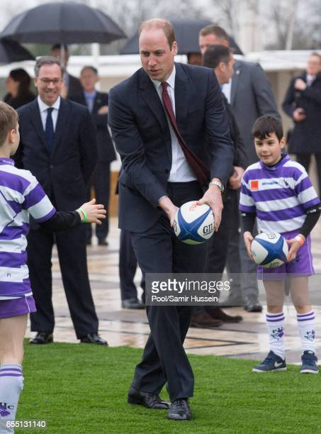 Prince William Duke of Cambridge plays rugby with young French rugby fans at the Trocadero square near the Eiffel Tower on March 18 2017 in Paris...