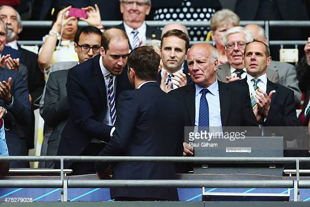 Prince William Duke of Cambridge presents Tim Sherwood manager of Aston Villa with a runnersup medal as FA Chairman Greg Dyke looks on after the FA...