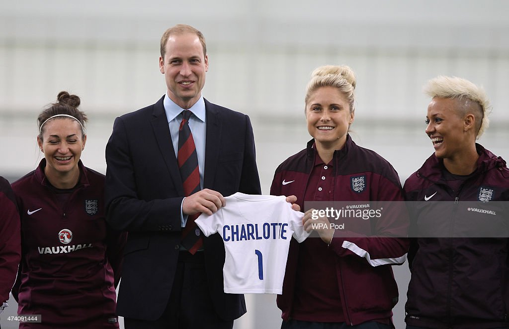 Prince William, Duke of Cambridge, President of the Football Association, is given an England shirt for Princess Charlotte during a visit to the England Women Senior Team at The National Football Centre at St. George's Park on May 20, 2015 in Burton-Upon-Trent, England.