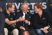 Prince William Duke of Cambridge Prince Charles Prince of Wales Prince Harry look at a mobile phone as they watch the athletics during the Invictus...