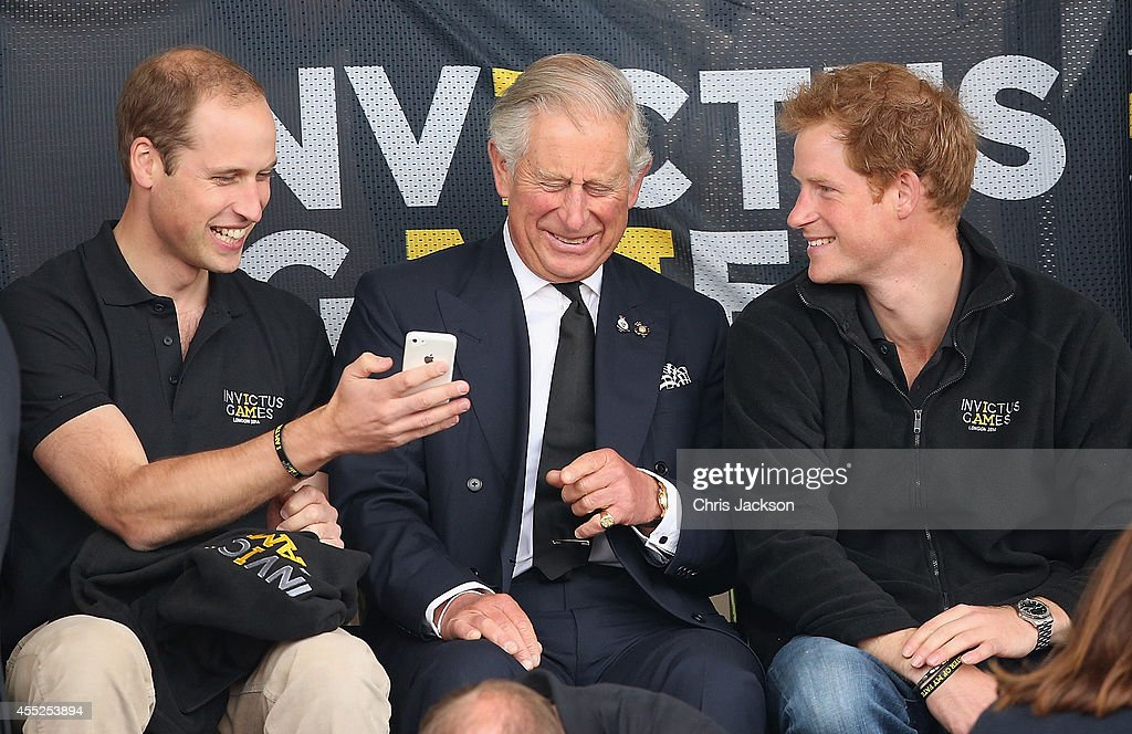 Prince William, Duke of Cambridge, Prince Harry and Prince Charles, Prince of Wales look at a mobile phone as they watch the athletics at Lee Valley Track during the Invictus Games on September 11, 2014 in London, England. The International sports event for 'wounded warriors', presented by Jaguar Land Rover, is just days away with limited last-minute tickets available at www.invictusgames.org