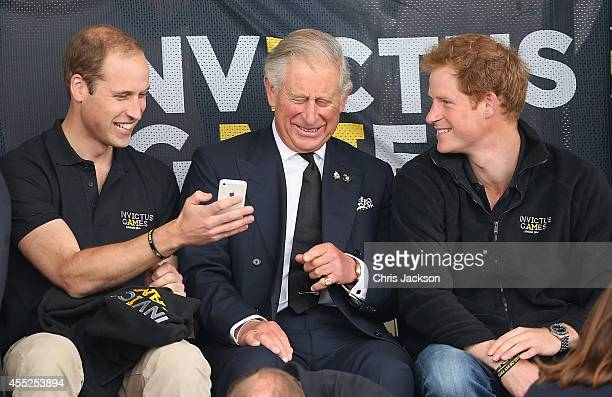 Prince William Duke of Cambridge Prince Harry and Prince Charles Prince of Wales look at a mobile phone as they watch the athletics at Lee Valley...