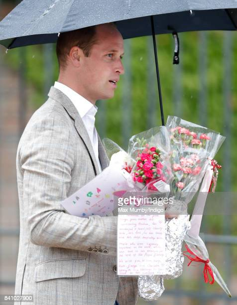Prince William Duke of Cambridge receives flowers from members of the public to place at the gates of Kensington Palace in tribute to Diana Princess...