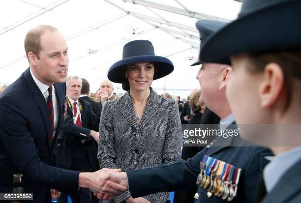Prince William Duke of Cambridge shakes hands as Catherine Duchess of Cambridge smiles as they meet veterans and serving members of the British armed...