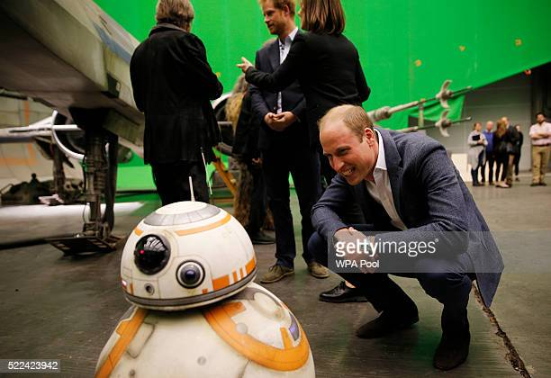 Prince William Duke of Cambridge smiles at the BB8 droid during a tour of the Star Wars sets at Pinewood studios on April 19 2016 in Iver Heath...