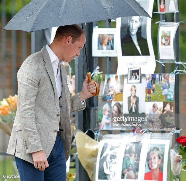 Prince William Duke of Cambridge views tributes to Diana Princess of Wales left at the gates of Kensington Palace after visiting the Sunken Garden on...