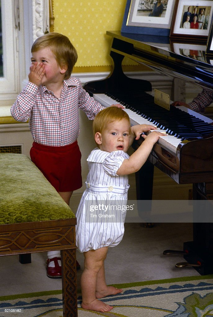 Prince William Giggling With His Hand Over His Mouth As He And His Baby Brother, <a gi-track='captionPersonalityLinkClicked' href=/galleries/search?phrase=Prince+Harry&family=editorial&specificpeople=178173 ng-click='$event.stopPropagation()'>Prince Harry</a>, Pretend To Play The Piano During A Private Photo Session At Their Home, Kensington Palace.