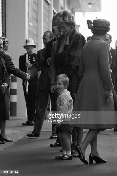 Prince William glances towards photographers as the Princess of Wales comes ashore from the Royal Yacht Britannia at Aberdeen Harbour