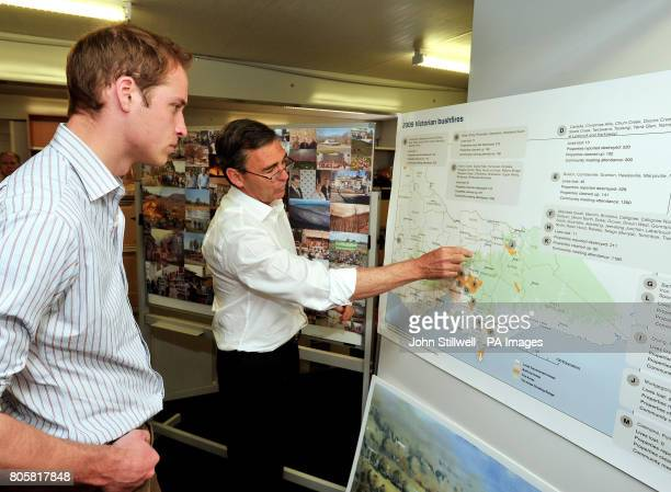 Prince William listens as John Brumby the Premier of Victoria in southern Australia points out on a map the area devasted by last year's forest fires...