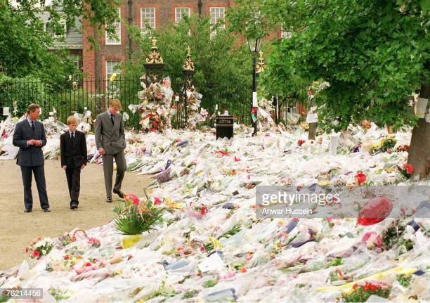 Prince William Prince of Wales with his sons Princes William and Harry looking at floral tributes left at Kensington Palace following the death of...
