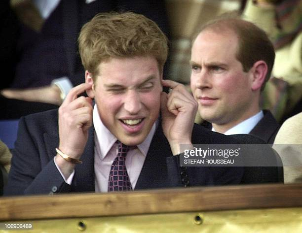 Prince William protects his ears from the noise of the 'Party at the Palace' in the gardens of Buckingham Palace in London 03 June 2002 as his uncle...