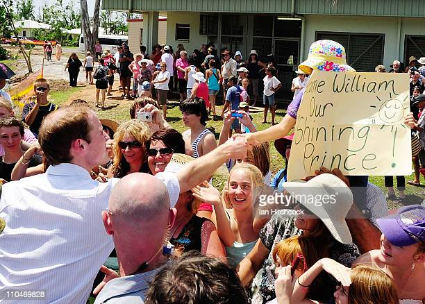 Prince William shakes hands with Jane Machan who made a sign for Prince William at the Cardwell Community Hall on March 19 2011 in Cardwell Australia...