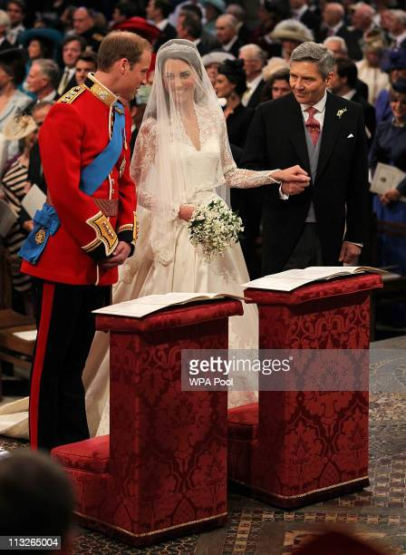 Prince William speaks to his bride Catherine Middleton as she holds the hand of her father Michael Middleton on April 29 2011 in London England The...