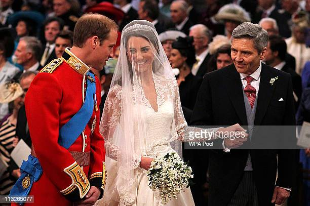 Prince William speaks to his bride Catherine Middleton as she holds the hand of her father Michael Middleton at Westminster Abbey on April 29 2011 in...