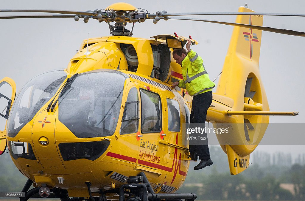Prince William, The Duke of Cambridge performs checks on his helicopter as he begins his new job with the East Anglian Air Ambulance (EAAA) at Cambridge Airport on July 13, 2015 in Cambridge, England. The former RAF search and rescue helicopter pilot will work as a co-pilot transporting patients to hospital from emergencies ranging from road accidents to heart attacks.